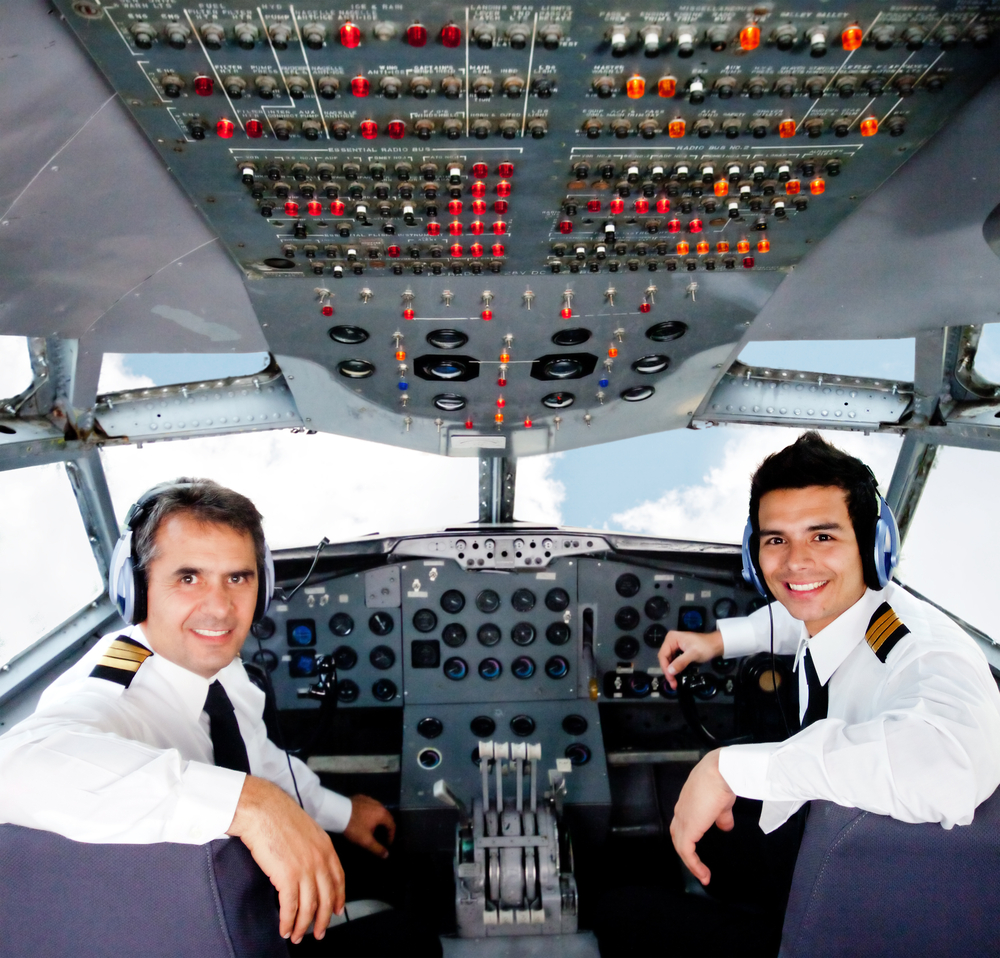 Pilots sitting in an airplane cabin flying on auto-pilot