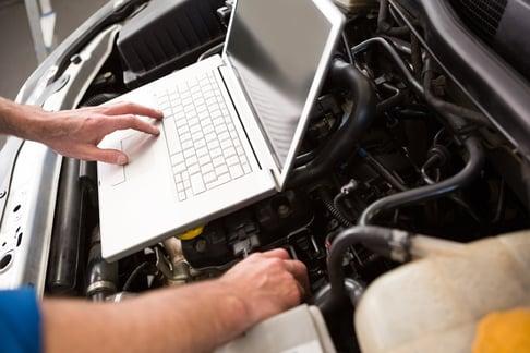 Dealer Mechanic servicing automotive engine at a  repair garage